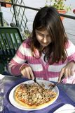 Little Girl Eats Pizza. A teen girl eats pizza by the river Royalty Free Stock Image