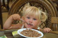 A little girl eats in a restaurant Royalty Free Stock Photo