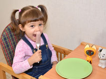 The little girl eats sausage by means of a fork Royalty Free Stock Photography