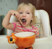 The little girl she eats with a spoon Stock Image