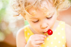 Little Girl eats sweet cherries Royalty Free Stock Photography