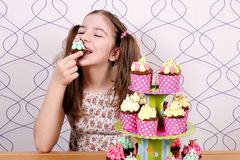 Little girl eats muffin Stock Images