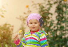 Little girl eats sweet yellow candy. Royalty Free Stock Images