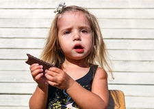 Little girl eats tasty chocolate Royalty Free Stock Image
