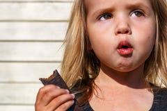Little girl eats tasty chocolate Stock Image