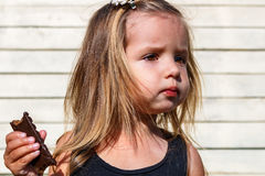 Little girl eats tasty chocolate Royalty Free Stock Photography