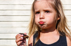 Little girl eats tasty chocolate Royalty Free Stock Photos