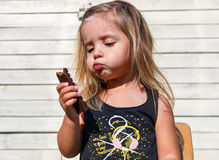 Little girl eats tasty chocolate Stock Photos