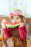 Little girl eats a  water-melon. Little girl in a straw hat with appetite eats a ripe water-melon Royalty Free Stock Image