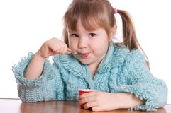The little girl eats yoghurt Stock Photos