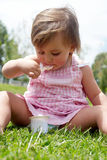 The little girl eats yoghurt sitting on a grass Royalty Free Stock Photo