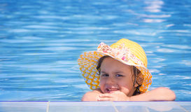 Little girl on the edge of the swimming pool Stock Images