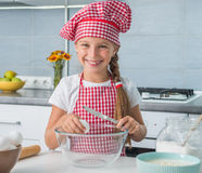 Little girl with egg and knife on kitchen Stock Photo