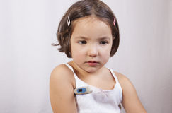 Little girl with electronic thermometer Royalty Free Stock Photo