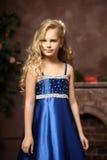 Little girl in an elegant blue dress. Blond little girl in an elegant blue dress Royalty Free Stock Images