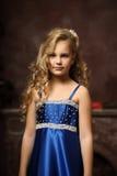Little girl in an elegant blue dress. Blond little girl in an elegant blue dress Royalty Free Stock Photo