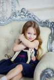 Little girl in an elegant dress sitting on a chair and hugging a toy horse Stock Photo