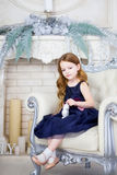 Little girl in an elegant dress sitting on a chair Stock Photos