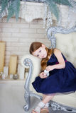 Little girl in an elegant dress sitting on a chair and looking at the camera Royalty Free Stock Images