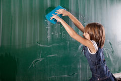 Little girl in elementary school cleaning board with spong. Math Stock Images