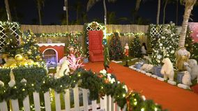 Little girl in elf costume dances in Christmas area. Santa`s helper is playing with toys. Baby celebrates, rejoices in. Christmas, decorates the Christmas zone stock video