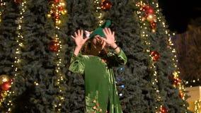 Little girl in elf`s costume dances, sings near the christmas tree. Santa`s helper celebrates, rejoices in Christmas in. Happy cute girl in elf costume dances stock video