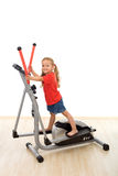 Little girl on elliptical trainer Stock Photography