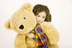 Little girl embraces a big teddy bear Royalty Free Stock Image