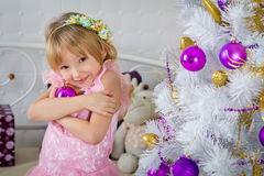 The little girl is embracing a bright ball near a Christmas  tre Royalty Free Stock Photography