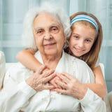 Little girl embracing grandmother Royalty Free Stock Photos