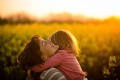 Little girl embracing her mom in the rapeseed field Royalty Free Stock Image