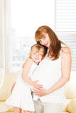 Little girl embracing her pregnant mother Stock Photography