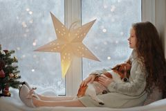 Little girl embracing her puppy dog sitting on window s and wait royalty free stock image