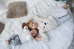 Cute girl with a newborn baby brother relaxing together on a white bed. Little girl embracing a newborn baby brother. Little girl and baby boy brother and sister stock images
