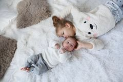 Cute girl with a newborn baby brother relaxing together on a white bed. Little girl embracing a newborn baby brother. Little girl and baby boy brother and sister stock photo