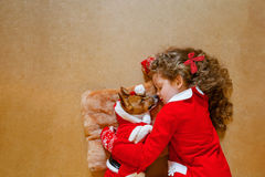Little girl embracing puppy dog. Stock Photos