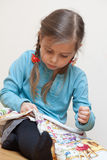 Little girl embroidering. Little girl working upon the embroidery Royalty Free Stock Photo