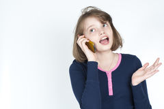 Little girl emotional talking on mobile phone. Royalty Free Stock Image