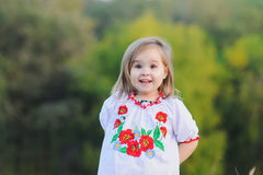 Little girl emotionally rejoices. Little 3-year-old girl  emotionally rejoices. A girl dressed in white Ukrainian national dress with embroidered flowers Royalty Free Stock Photo