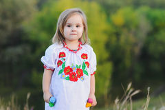 Little girl emotionally rejoices. Little 3-year-old girl. A girl dressed in white Ukrainian national dress with embroidered flowers Stock Photo