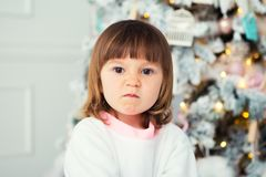 Little girl emotions. Brooding and grimace. Problem of choice. Close-up in the interior. Little girl emotions. Brooding and grimace. Problem of choice. Close-up Royalty Free Stock Image