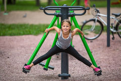 Little girl is engaged in fitness equipment outdoor. Sport. Royalty Free Stock Photo