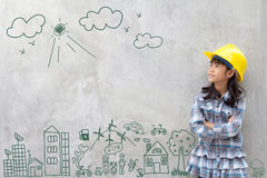 Little girl engineering with creative drawing environment. With happy family, eco friendly, save energy, against a brick wall Stock Image