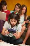 Little Girl Engrossed In Gaming. Little Caucasian girl focused on her portable gaming console Royalty Free Stock Photo