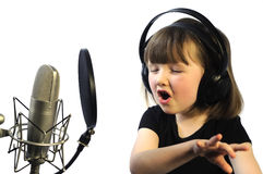Little girl engrossed in singing. Little girl engrossed in recording a song Royalty Free Stock Images