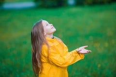 Little girl enjoy the rain on warm autumn day Stock Photo