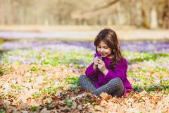 Girl inspired by nature. Little girl enjoy the sun, she is gathering the flowers, inspired by blossom meadow of saffrons Stock Photo