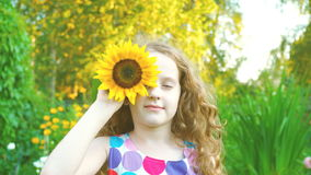 Little girl enjoy with sunflowers in summer park. Curly haired little girl enjoy with sunflowers in summer park stock footage