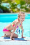 Little active adorable girl in outdoor swimming pool ready to swim. Little girl enjoy vacation in the swimming pool stock photo