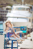 Little girl enjoying beautiful day near city harbor Royalty Free Stock Image